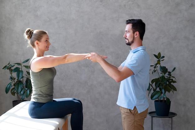 Fizjoterapeuta pomaga kobiecie średniego strzału