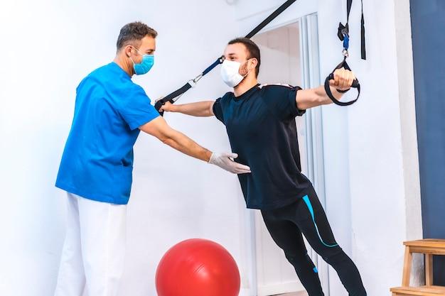 Fizjoterapeuta pomaga pacjentowi rozciągając gumki do góry nogami. fizjoterapia ze środkami ochronnymi przeciwko pandemii koronawirusa, covid-19. osteopatia, sportowy kręgarz
