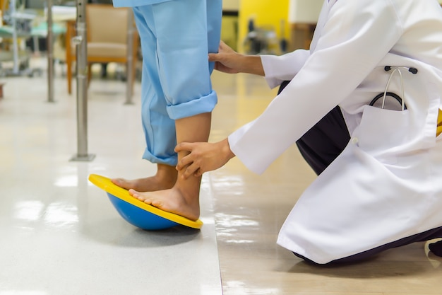 Fizjoterapeuta pomaga pacjentowi w ćwiczeniu równoważenia się przy użyciu sprzętu.