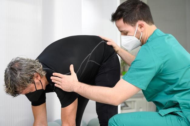 Fizjoterapeuta pomaga pacjentowi w klinice.