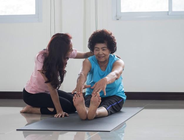 Fizjoterapeuta pomaga seniorowi w ćwiczeniach