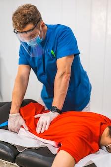 Fizjoterapeuta pracujący na biodrze pacjenta. fizjoterapia ze środkami ochronnymi przeciwko pandemii koronawirusa, covid-19. osteopatia, terapeutyczny chiromasaż
