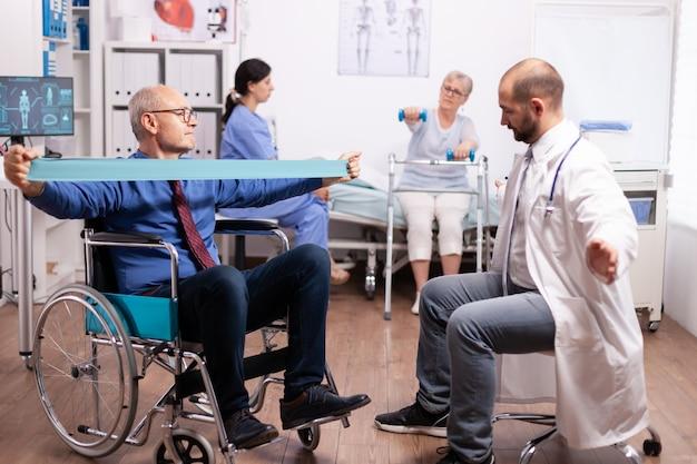 Fizjoterapeuta pracujący z niepełnosprawnym starszym mężczyzną w nowoczesnej klinice osoby w podeszłym wieku z inwalidztwem w szpitalu po leczeniu rehabilitacyjnym z pomocą personelu medycznego