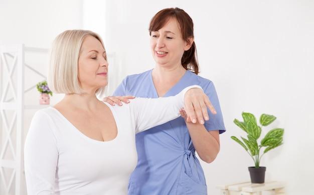 Fizjoterapeuta pracuje z pacjentem w średnim wieku w klinice