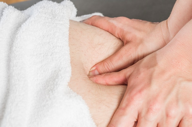 Fizjoterapeuta robi masaż ścięgien udowych do pacjenta mężczyzna.