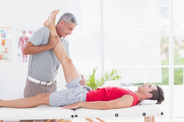 Fizjoterapeuta robi nogę rozciągając do jego pacjenta