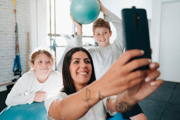 Fizjoterapeuta robi selfie z dziećmi, do których uczęszcza podczas konsultacji, gdy są kontuzjowane