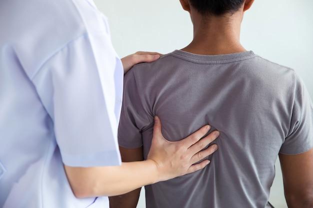 Fizjoterapeuta robi zabiegi lecznicze na plecach mężczyzny.