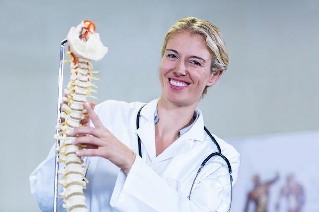 Fizjoterapeuta trzyma model kręgosłupa
