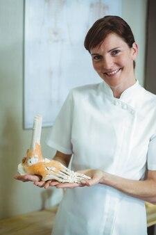 Fizjoterapeuta trzyma model szkieletu stóp