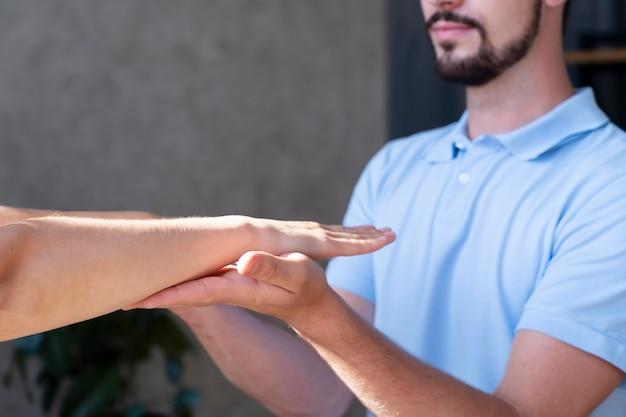 Fizjoterapeuta trzymający się za ręce z bliska