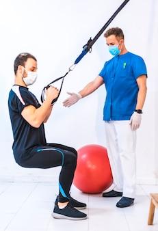 Fizjoterapeuta w niebieskiej sukni i pacjent w przysiadu, pracujący na rękach za pomocą gumek. fizjoterapia ze środkami ochronnymi przeciwko pandemii koronawirusa, covid-19. osteopatia, sportowy kręgarz