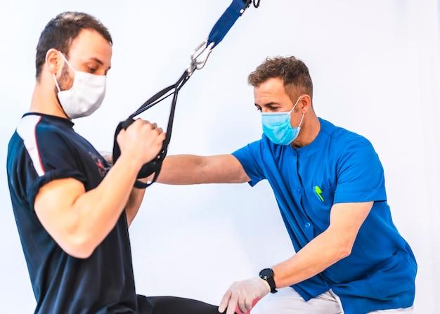 Fizjoterapeuta w niebieskiej sukni z pacjentem ćwiczeń z rękami. fizjoterapia ze środkami ochronnymi przeciwko pandemii koronawirusa, covid-19. osteopatia, sportowy kręgarz