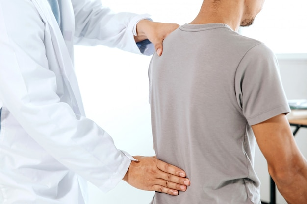 Fizjoterapeuta wykonujący leczenie uzdrawiające na plecach mężczyzny. ból pleców, masażysta
