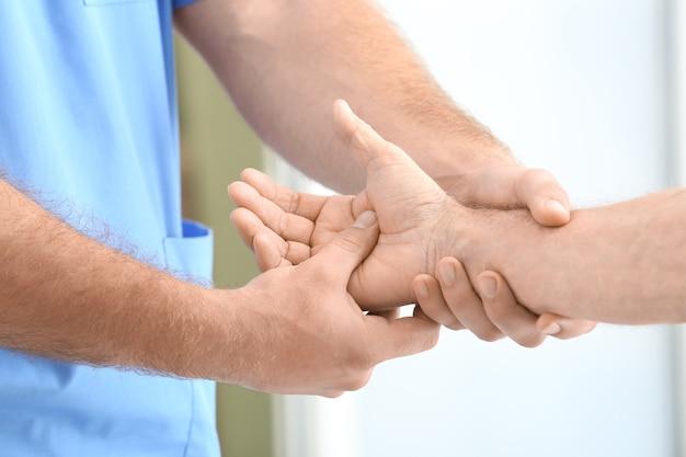 Fizjoterapeuta wykonujący masaż dłoni starszego mężczyzny w klinice