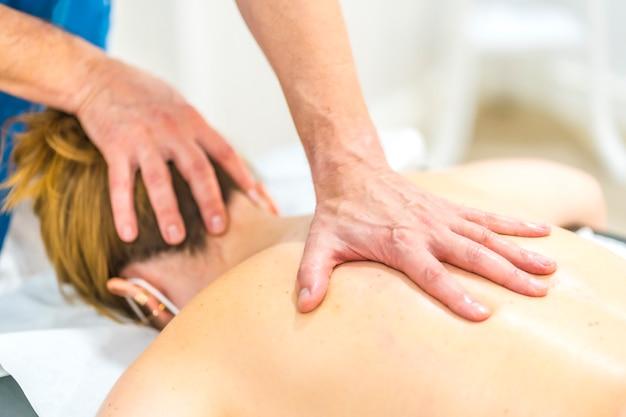 Fizjoterapeuta wykonuje masaż jedną ręką na plecach dziewczyny z maską. środki bezpieczeństwa fizjoterapii w pandemii covid-19. osteopatia, terapeutyczny chiromasaż