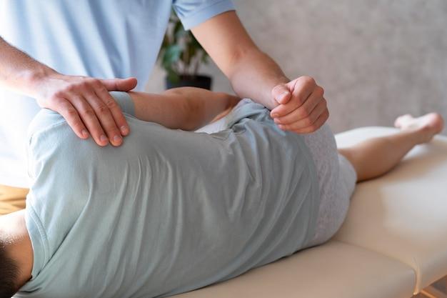 Fizjoterapeuta z bliska pomaga pacjentowi z bólem