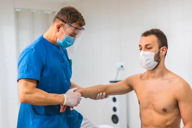 Fizjoterapeuta z ekranem i maską dający masaż nadgarstka pacjentowi z maską. fizjoterapia ze środkami ochronnymi przeciwko pandemii koronawirusa, covid-19. osteopatia