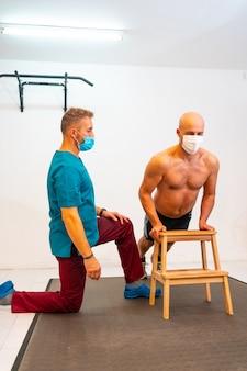 Fizjoterapeuta z maską na twarz i pacjentką wykonującą pompki. fizjoterapia ze środkami ochronnymi przed pandemią koronawirusa, covid-19. osteopatia, quiromasaż sportowy