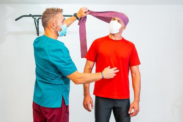 Fizjoterapeuta z maską na twarz napinającą szyję pacjenta gumką. fizjoterapia ze środkami ochronnymi przed pandemią koronawirusa, covid-19. osteopatia, quiromasaż sportowy