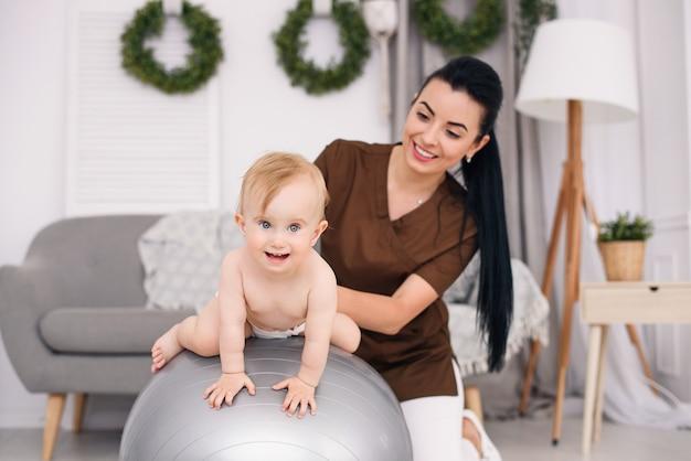 Fizjoterapeuta z szczęśliwym dzieckiem robi ćwiczenia z piłką gimnastyczną w sali medycznej. pojęcie opieki zdrowotnej i medycznej.