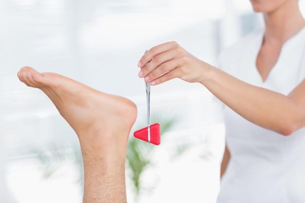 Fizjoterapeuta za pomocą młotka odruchowego