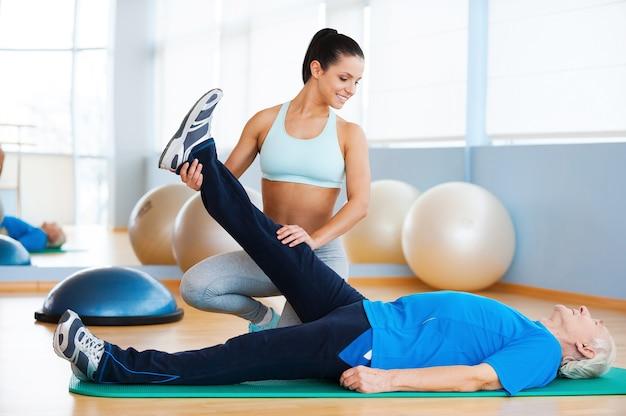 Fizjoterapia. pewna siebie fizjoterapeutka pracująca ze starszym mężczyzną w klubie fitness