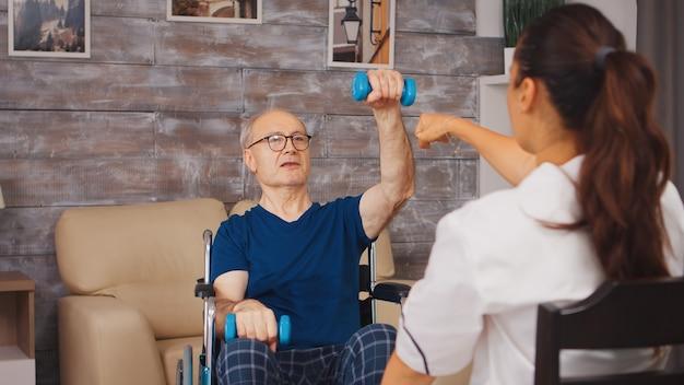 Fizjoterapia starszy mężczyzna na wózku inwalidzkim z pomocą pracownika medycznego. osoba starsza niepełnosprawna niepełnosprawna z pracownikiem socjalnym w okresie rekonwalescencji terapia rehabilitacyjna fizjoterapia służba zdrowia opieka pielęgniarska emerytura