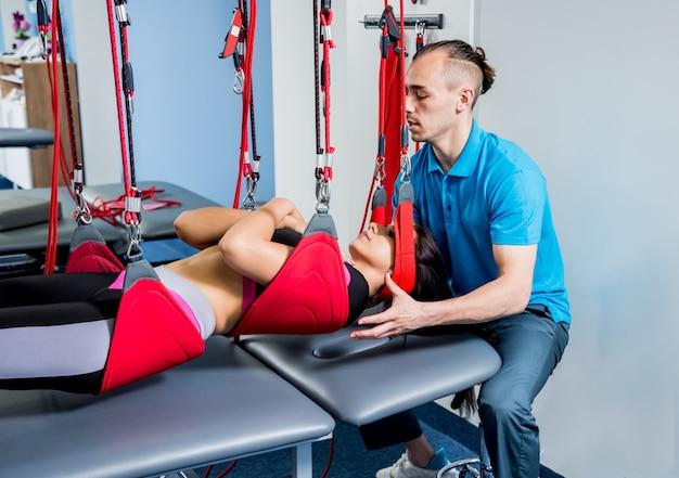 Fizjoterapia. terapia treningu zawieszenia. młoda kobieta robi trakcji fitness