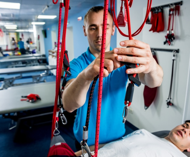 Fizjoterapia. terapia treningu zawieszenia. młody człowiek robi trakcji fitness