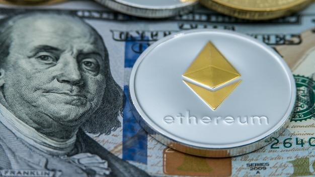 Fizyczna metalowa srebrna waluta ethereum o wartości ponad 100 dolarów amerykańskich. wirtualne pieniądze w internecie na całym świecie z banknotami usa. cyberprzestrzeń na monety cyfrowe, kryptowaluta eth. płatność online