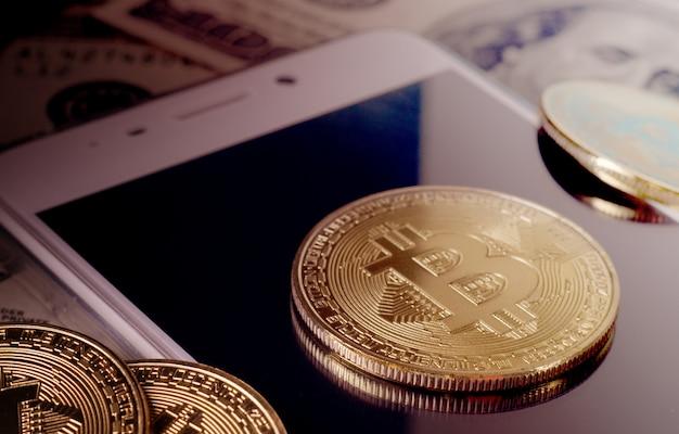 Fizyczna złocista bitcoin moneta przeciw dolarowym rachunkom i smartphone na purpurowym tle.
