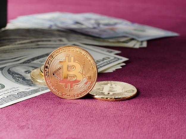 Fizyczna złocista bitcoin moneta przeciw dolarowym rachunkom na purpurowym tle.