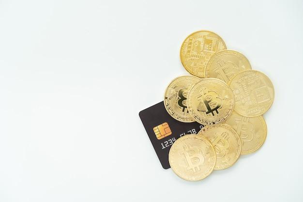 Fizyczna złota moneta kryptowaluty bitcoin - btc i karta kredytowa, makieta karty kredytowej, na białym tle z copyspace. koncepcja inwestycji w aktywa cyfrowe i kryptowaluty.