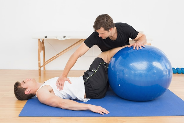 Fizyczny terapeuta pomaga młodego człowieka z joga piłką