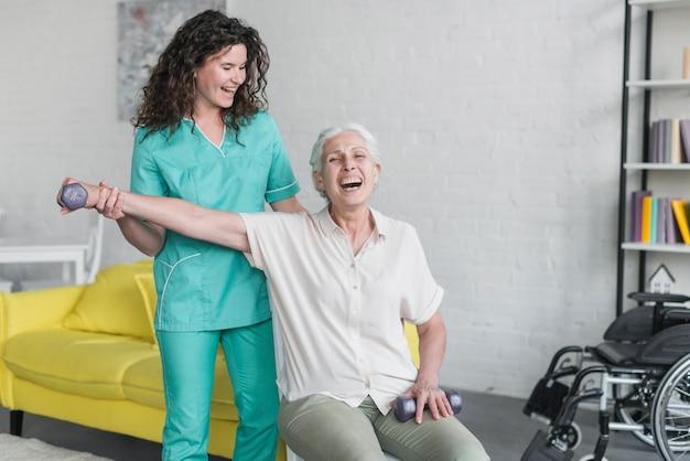 Fizyczny terapeuta pomaga starszej kobiety dla robić ćwiczeniu z dumbbell