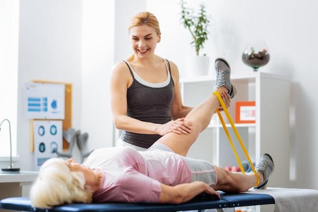 Fizykoterapia. przyjemna wesoła kobieta uśmiecha się do pacjenta, podnosząc rękę do góry