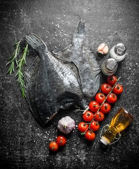 Flądra surowa rybna z pomidorkami koktajlowymi, przyprawami i czosnkiem. na ciemny rustykalny