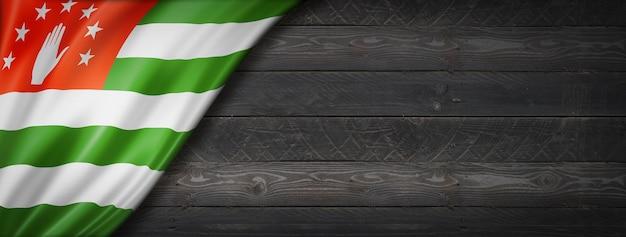 Flaga abchazji na czarnej ścianie z drewna. poziomy baner panoramiczny.