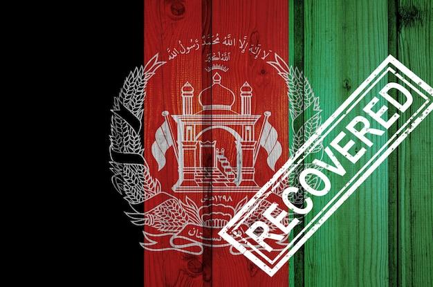 Flaga afganistanu, która przeżyła lub wyzdrowiała z infekcji epidemii koronawirusa lub koronawirusa. flaga grunge z pieczęcią odzyskane