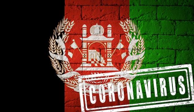 Flaga afganistanu o oryginalnych proporcjach z pieczęcią koronawirusa. cegła ściana tekstur. koncepcja wirusa koronowego. na skraju pandemii covid-19 lub 2019-ncov.