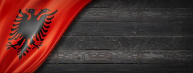 Flaga albanii na czarnej ścianie z drewna