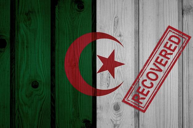 Flaga algierii, która przeżyła lub wyzdrowiała z infekcji epidemii koronawirusa lub koronawirusa. flaga grunge z pieczęcią odzyskane