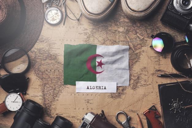 Flaga algierii między akcesoriami podróżnika na starej mapie vintage. strzał z góry