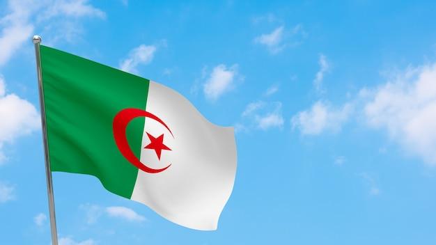 Flaga algierii na słupie. niebieskie niebo. flaga narodowa algierii