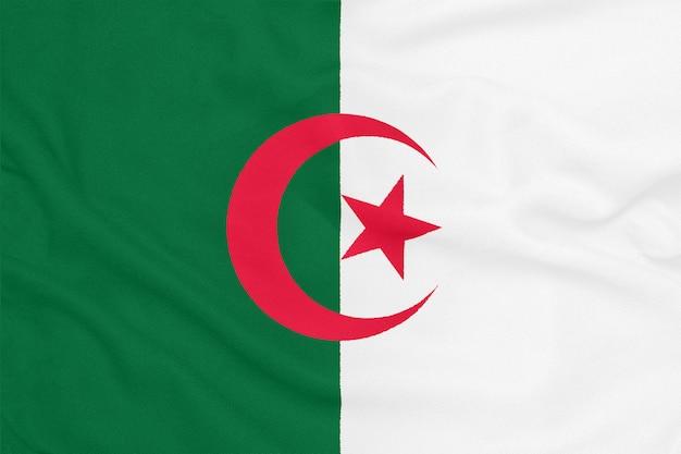 Flaga algierii na teksturowanej tkaninie. symbol patriotyczny