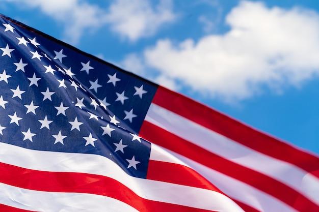 Flaga amerykańska macha na wietrze przeciw niebieskiemu niebu