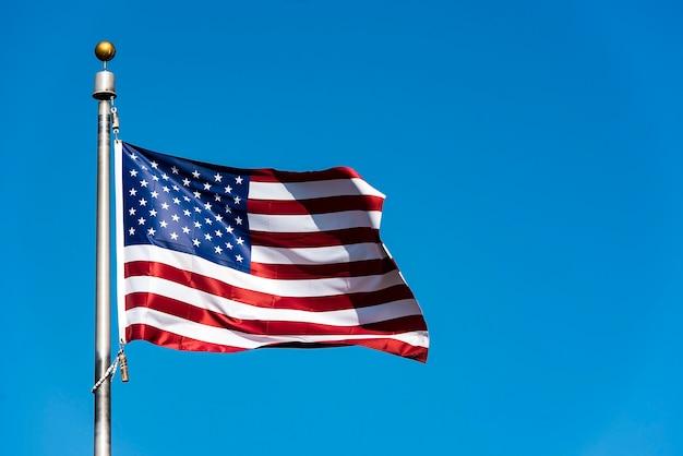 Flaga amerykańska macha przeciw błękitne niebo, usa flaga macha