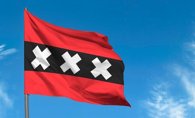 Flaga amsterdamu na tle błękitnego nieba