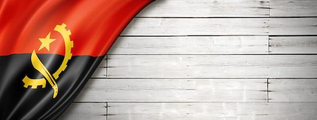 Flaga angoli na starej białej ścianie. poziomy baner panoramiczny.